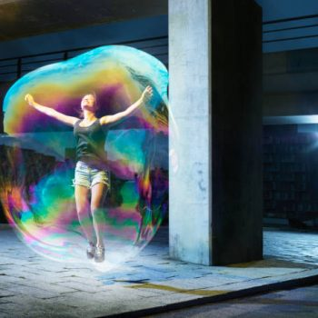 young female in soapbubble, full body, in urban environment
